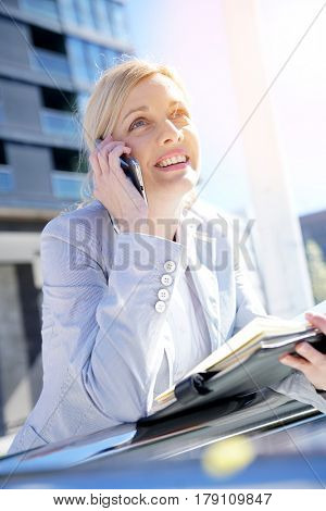 Portrait of businesswoman talking on phone outside the office
