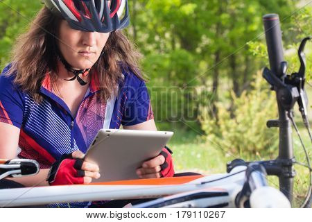 Mountainbiker With Her Tablet In Nature