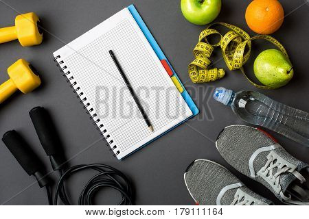 Workout plan with fitness food and sport equipment on gray background, top view. Copy space. Still life flat lay