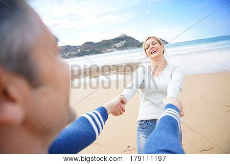Middle-aged couple on the beach having fun turning around