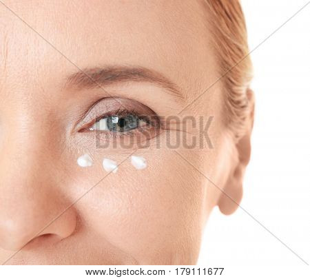 Senior woman with facial anti-aging cream on white background