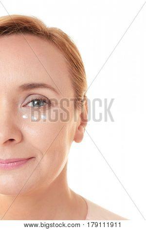 Senior woman with facial anti-aging cream on white background