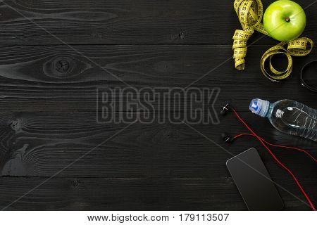 Workout plan with fitness equipment on dark background, top view. Copy space. Still life