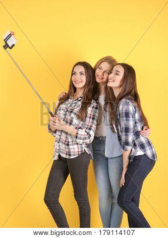 Beautiful young women taking selfie near color wall