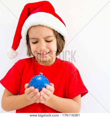 Cute little kid with decoration ball wearing Santa hat and smiling