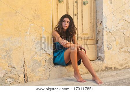 Beautiful young woman sitting leaning against an entrance door