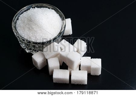 Top view on a Bowl with white granulated and refined sugar on black surface close-up