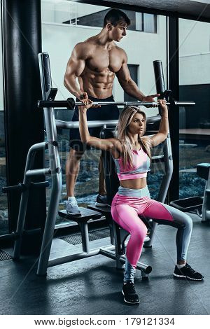 Fitness instructor exercising with his client at the gym. Young woman doing exercises with a bar under the supervision of a coach