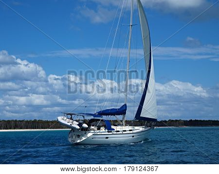 A picturesque tropical sailing image off pristine Coongul Beach with blue sky and white cloud on Fraser Island Queensland Australia. Photographed from Hervey Bay.