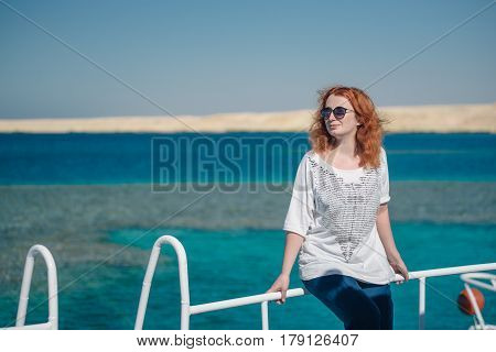 Beautiful ginger woman in sun glasses sits on a white yacht in a sea with clear turquoise water. Relaxation at summer vacation under a sun. Woman looks away.