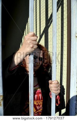 Woman with black sunglasses standing behind bars