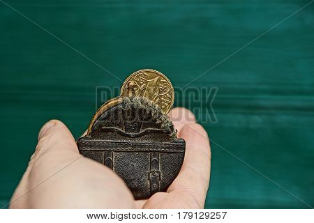 A small purse and a coin on the palm of your hand