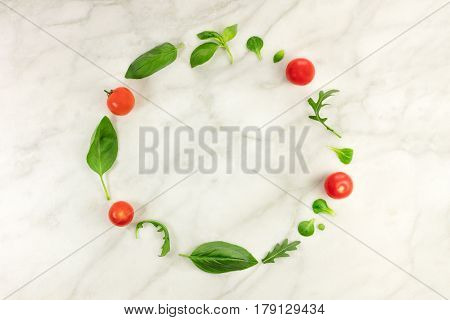 A frame made up by fresh green herbs including basil leaves, corn salad, and ruccola, with cherry tomatoes, shot from above on a while marble table with a place for text