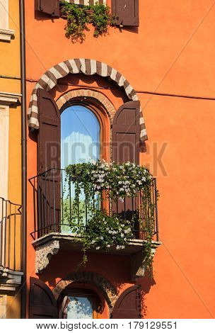 Decorated window on orange colored building in south Europe