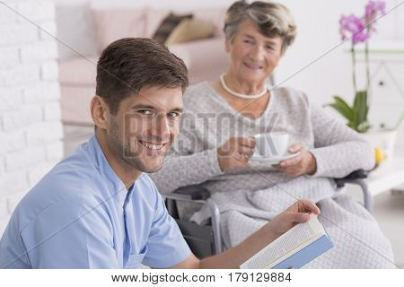 Caregiver Reading To Senior Lady With Tea