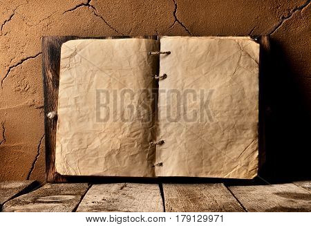 Opened old book on table near clay wall