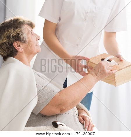 Carer Giving Tissues To Senior Lady