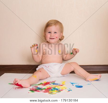 Happy baby drawing with her fingers sitting on the floor. Toddler painting. Finger paints for babies.