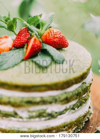 The part of the tasty sponge green and white cake with strawberries and mint placed on the wooden stump in the wood. The close-up composition