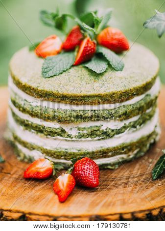 The close-up photo of the sponge wedding green and white cake with strawberries and mint placed on the wooden stump. A couple of strawberries are lying in the front of the cake
