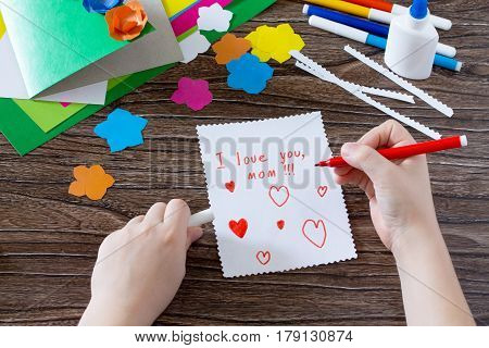 Greeting Card With Flowers On Matter Day. The Child Writes An Inscription Saying That I Love You. Ch