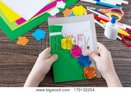 A Child Is Holding A Greeting Card With Flowers On Mother's Day. Children's Art Project, Craft For C