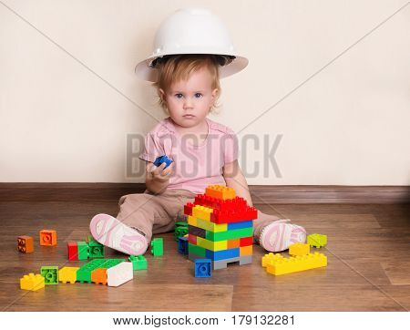 Adorable little builder. Cute baby in protective helmet playing with plastic constructor blocks building a house.