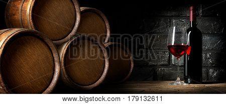 Red wine near barrels in cellar of winery