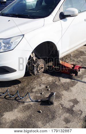 Car Without Wheel And Lift Up By Hydraulic, Waiting For Tire Replacement
