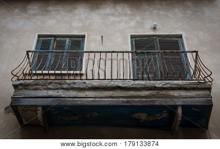 Apartment Balcony with blue wooden doors in a bad condition ready to collapse