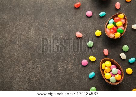 Easter chocolate eggs with colorfull candies on chalkboard with free space for congratulation text.