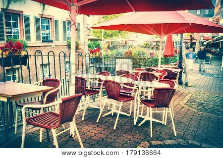 Cafe terrace in small European city. City street background