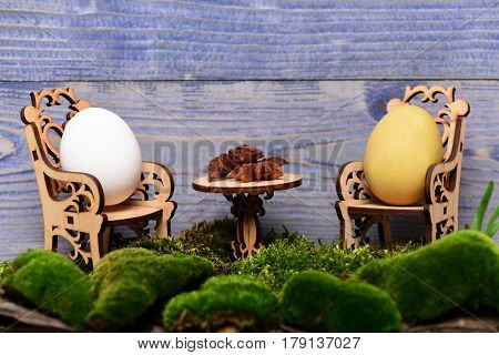 Easter Egg In Wooden Chairs At Table With Badian, Moss