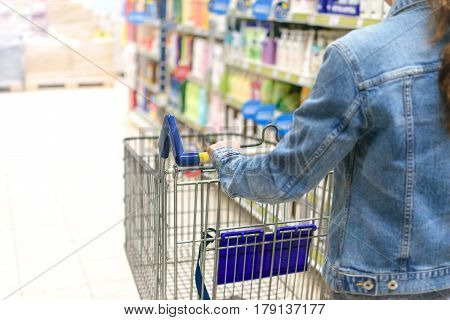 Young woman pushing empty shopping cart in a supermarket