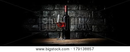 Bottle and glass of wine near black wall