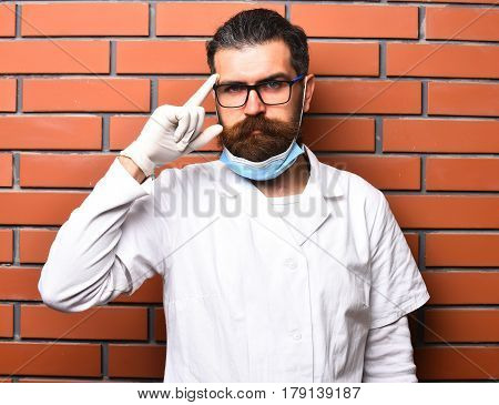 Bearded man long beard. Brutal caucasian doctor or unshaven hipster postgraduate student in medical gown glasses and gloves on brown brick wall studio background. Medicine concept poster