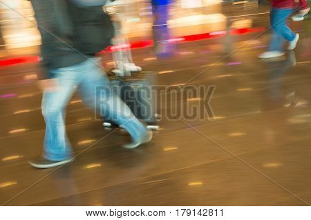 hurry people tourists with travel suitcase or bag luggage in airport or station as blurred or defocused background in speed motion