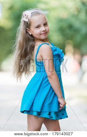 small baby girl or cute child with adorable smiling face and bow in blonde hair in blue dress outdoor on blurred background