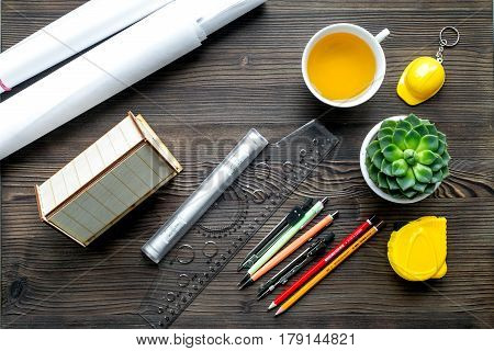 Construction office with architect working tools and cup of tea on wooden table background top view