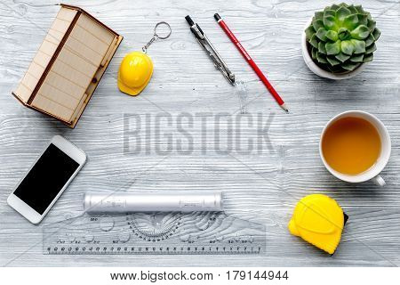 architect working desk with cup of tea, phone and ruler on light wooden background top view mock up