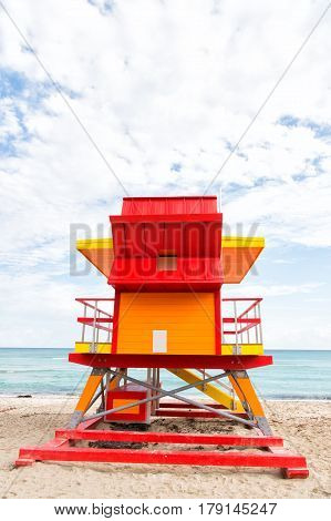 Miami south beach. colorful lifeguard house or lifesaving art deco tower building red and orange color on sandy beach near sea ocean water on cloudy sky background Traveling and vacation