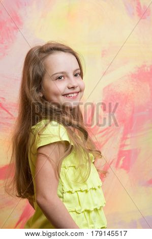 small baby girl or cute child with happy face and blonde hair in yellow shirt on colorful abstract background