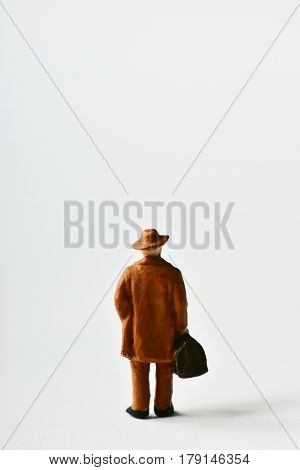 miniature traveler man seen from behind wearing a hat and carrying a suitcase, on an off-white background with a blank space above it