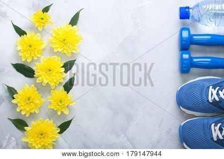 Summer spring flatlay sports composition blue sneakers dumbbells bottle of water yellow chrysanthemums green leaves gray concrete background. Concept healthy lifestyle sport diet in summer spring. Horizontal orientation top view place for copyspace.