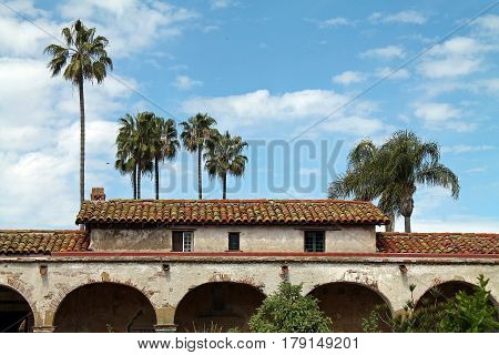 Adobe Casita with Red Tile Roof and Palm Trees in the Background