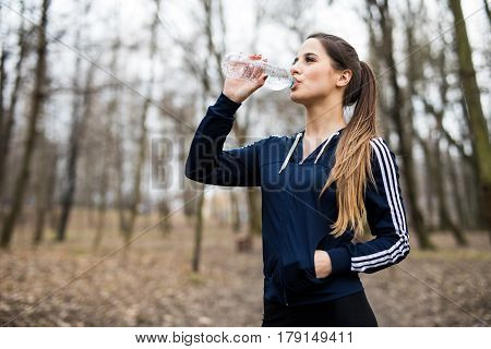 Young woman drinking water after jogging running