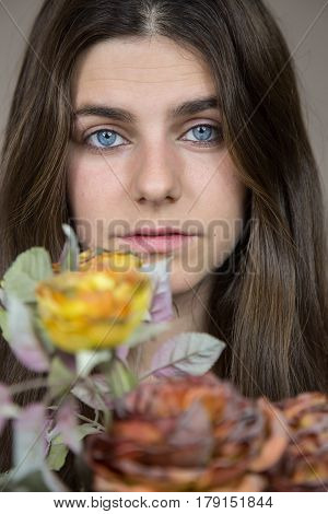 Portrait of a beautiful young white girl with blue eyes and brown hair holding a bouquet of dried flowers. She has a serious look and a little sad.
