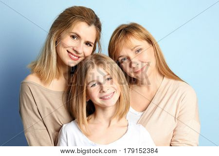 Cute girl with her mother and granny on color background
