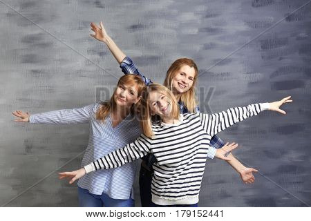 Cute girl with her mother and granny near color wall