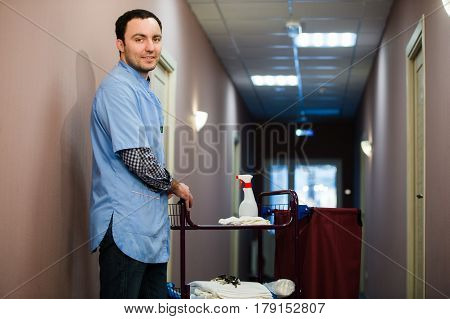A man who is on the hotel cleaning crew staff is smiling with a towel, pillow and vacuum in the process of cleaning the hotel rooms and delivering top-knotch service to the guests